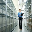 Businesswoman standing in warehouse with clipboard next to metallic shelves — Stock Photo #27521519