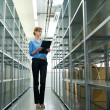 Female worker with clipboard, oraganizing inventory and stock in warehouse — Stock Photo