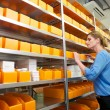 Female pharmacy worker looking at shelves for drugs and medicine — Stock Photo