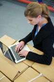 Business woman typing on laptop in warehouse — Stock Photo