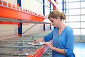 Zaměstnanec skladu ženské stojící vedle regálech a psaní na schránky — Stock fotografie
