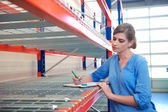 Female worker writing inventory at delivery depot warehouse — Stock Photo