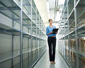 Businesswoman standing in warehouse with clipboard next to metallic shelves — Stock Photo