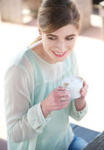 Young woman smiling and enjoying a cup of coffee — Stock Photo