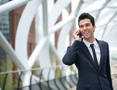 Smiling business man talking on mobile phone in the city — Stock Photo