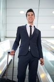 Attractive young businessman traveling with bag — Stock Photo