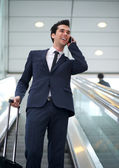 Attractive young businessman talking on mobile phone — Stock Photo