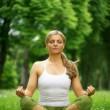 Woman sitting in yoga pose meditation outdoors — ストック写真