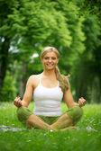 Mujer sonriendo y sentado en posición de yoga en el parque — Foto de Stock