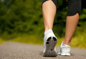 Female walking outdoors in running shoes — Stock Photo