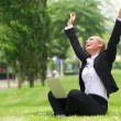 Successful businesswoman with laptop and arms outstretched — Stock Photo