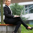 Beautiful business woman working with laptop in park — Stock Photo