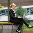 Happy businesswoman working on laptop in the city — Stock Photo