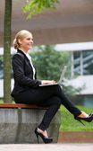 Businesswoman smiling and working outdoors on laptop — Stock Photo