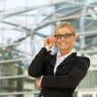 Happy businesswoman smiling with glasses in the city — Stock Photo #28857545