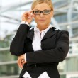 Young business woman with glasses standing outdoors — Stock Photo