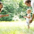 Happy young family teaching baby to walk — Stock Photo #28890901