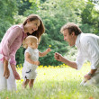 Stock Photo: Happy family with child giving flower to father