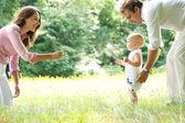 Glad ung familj undervisning babyn att gå — Stockfoto