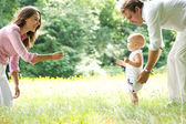 Happy young family teaching baby to walk — Stock Photo