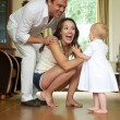 Happy parents helping baby take first steps — Stock Photo