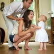 Happy family smiling at baby standing at home — Stock Photo