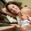Happy mother smiling as baby plays piano — Stock Photo #28937165