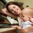 Happy mother smiling as baby plays piano — Stock Photo