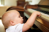 Cute baby playing on piano — Stock Photo