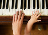 Adult hand playing piano with baby hand — Stock Photo