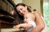 Mother smiling as baby plays piano — Stock Photo