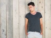 Good looking young man standing outdoors against wall — Stock fotografie