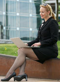 Businesswoman typing on laptop outdoors in the city — Stock Photo