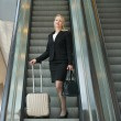 Business woman standing on escalator with travel bags — Stock Photo