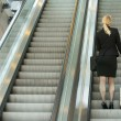 Businesswoman standing on escalator with travel bags — Stock Photo #29064463