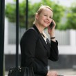 Businesswoman sitting outdoors and calling by phone — Stock Photo