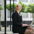 Businesswoman working on laptop outdoors — Stock Photo