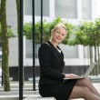 Businesswoman typing on laptop outdoors — Stock Photo