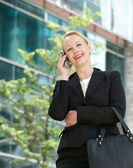 Happy businesswoman talking on cellphone outdoors — Stock Photo