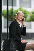 Affärskvinna sitter utomhus och ringer via telefon — Stockfoto