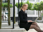 Businesswoman smiling with laptop outside — Stock Photo