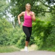 Fit young woman running in the park — Stockfoto