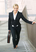 Confident business woman walking upstairs with bag — Stock Photo