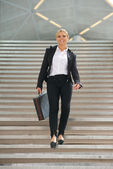 Happy business woman walking downstairs with briefcase — Stock Photo