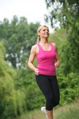 Athletic young woman running outdoors — Foto Stock