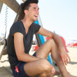 Happy young man sitting at the beach — Stock Photo