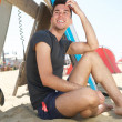 Attractive young man sitting at the beach — Stock Photo #29234059