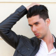 Portrait of a handsome young man with hand in hair — Stock Photo