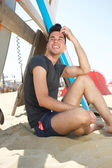 Attractive young man sitting at the beach — Stock Photo