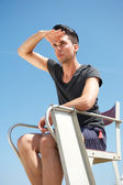 Male life guard sitting on chair on a summer day — Stock Photo